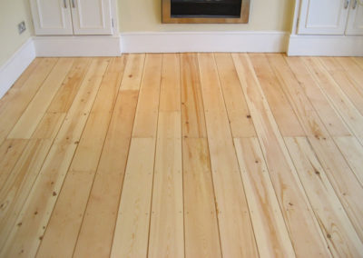 After - pine tongue and groove floorboards with gaps filled and varnished